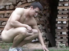 Strong young twink is doing work at yard nude